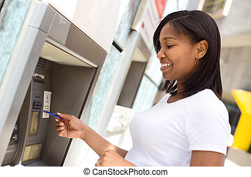 girl at the atm - young woman at the cash machine...