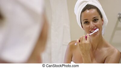 Young woman cleaning her teeth with a toothbrush in the...