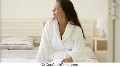 Happy friendly young woman in a white bath robe sitting on...
