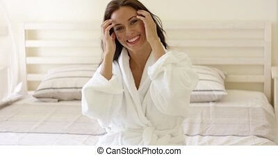 Vivacious young woman with a lovely smile sitting on her bed...