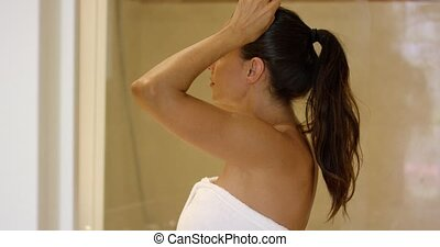 Side view on woman fixing hair in bathroom - Side view on...