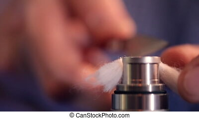 Trim ends of wick from wool of electronic cigarette closeup....