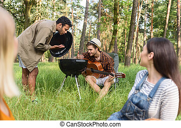 Cute friends preparing barbecue in nature - Joyful guys are...