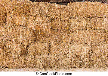 stack of straw or hay bales in a rural landscape