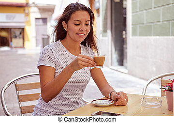 Relaxed girl drinking coffee at street cafe