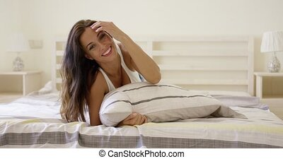 Woman with cheerful expression laying down on bed - Single...