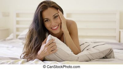 Happy young woman cuddling up in bed hugging the pillow to...
