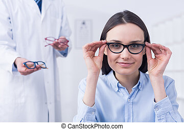 Woman choosing the perfect glasses - Smiling petty young...