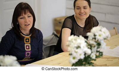 Two women discuss project designer for behind wooden table...