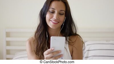 Beautiful young woman listening to music on a storage device...