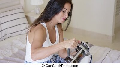 Attractive young woman pouring fresh coffee from a filter...