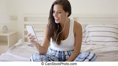 Giggling woman using device with ear buds in bed - Giggling...