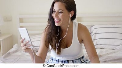 Happy woman listening with ear buds and tablet - Laughing...