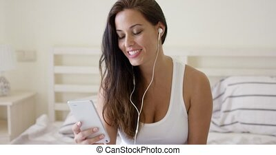 Laughing woman using device with ear buds in bed - Laughing...