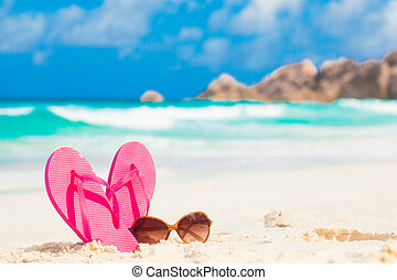 Pink flip flops and sunglasses on a tropical sea resort background