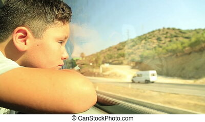 Sad child looking out window - Tired little boy travelling...