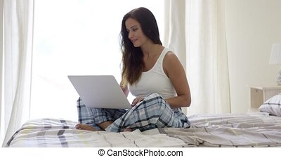 Smiling woman using laptop in bed - Single smiling woman in...