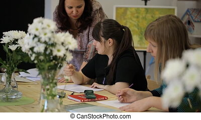 Women pencil draw white flowers in a vase, drawing courses together with teacher.