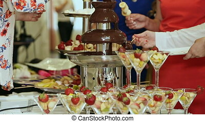People dipped strawberries in chocolate fountain. Celebration.