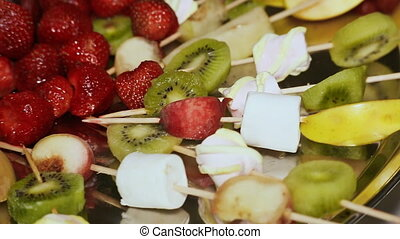 Pieces of Fruit, strawberries, a kiwi, apple and fruit jelly lie on a plate