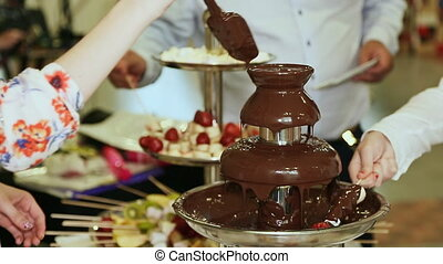 People dipped strawberries in chocolate fountain - Vibrant...