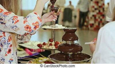 People dipped strawberries in chocolate fountain.