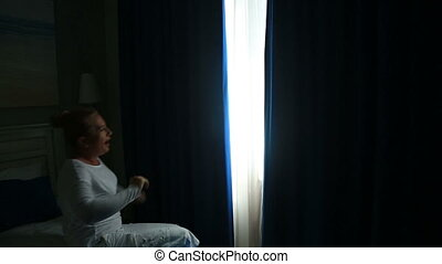 Woman wake up and opens the curtain - Woman is awoke and...