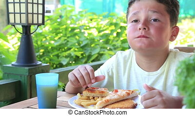 Child eating pizza and french fries