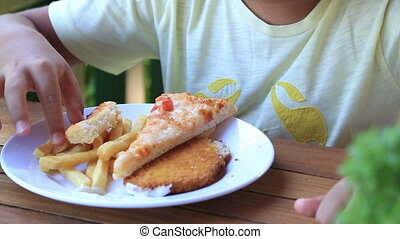 Boy eating pizza and french fries - Cute boy eating pizza...