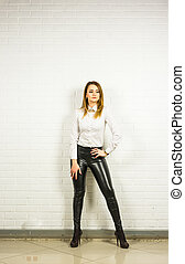 Woman wearing black leather pants and high heel shoes...