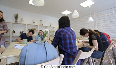 Light blue backpack lies on wooden chair in art studio. This...