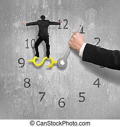 Man balancing on USD clock hand with another holding,...