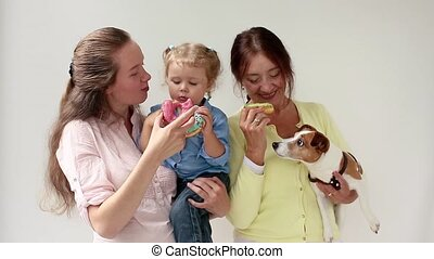 Family, three women eating donuts and dog on a white...