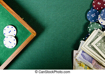 Poker chips and money on a green poker table