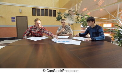 Handsome men sit at round wooden table and discuss plan of...