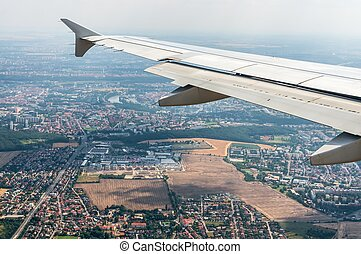 Looking through window airplane on a wing and city of Prague
