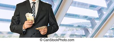 Man in business suit with money in office