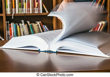 The hand opening and browsing the book pages - The hand of a...