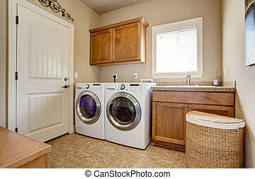 Laundry room with washer and dryer. Wooden cabinets and tile...