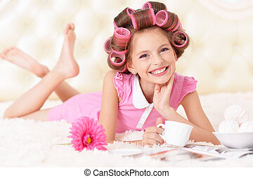 Little pretty girl in hair curlers - portrait of happy...