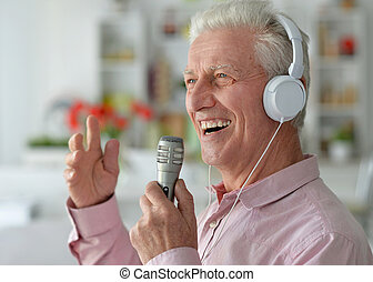 Senior man singing - Portrait of a senior man singing into...