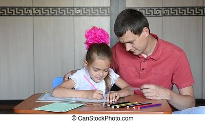 Girl and father first grader solving homework joyfully...