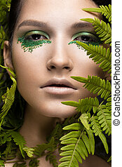 Beautiful girl with art make-up, fern leaves. The beauty of...