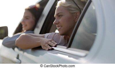 happy teenage girls or women in car at seaside 1 - summer...
