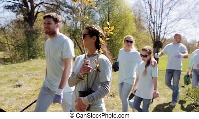 group of volunteers with tree seedlings in park -...