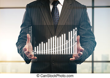 Businessman holding abstract business chart on blurry window...