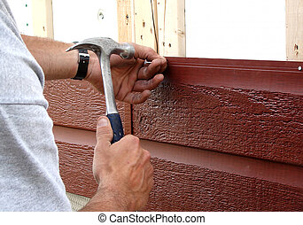 Nailing siding - Action shot of a construction worker...