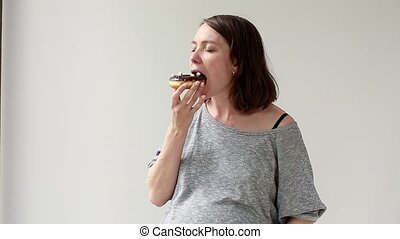 Pregnant woman eating junk food Girl eat delicious chocolate...