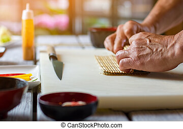 Mans hands holding bamboo mat Cooking board on wooden...