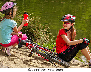Children bicycle have rest near water in park outdoor.